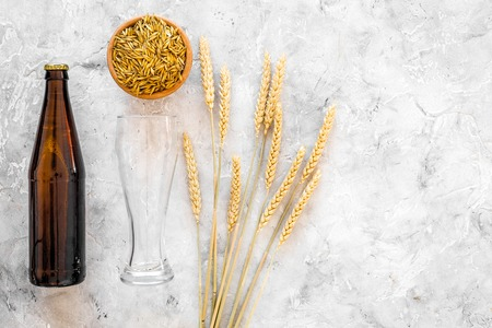 Ingredients for beer. Malting barley near beer glasses and bottle on grey background top view. Stock Photo - 86960197