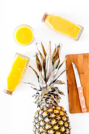 Ananassap in glasfles dichtbij gehele ananas op witte hoogste mening als achtergrond.