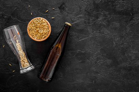 Preparing beer. Barley near beer bottle and glass on black background top view copyspace