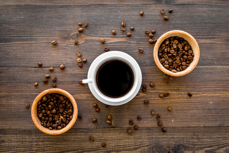 Cup of black coffee near coffee beans on wooden background top view. Stock Photo