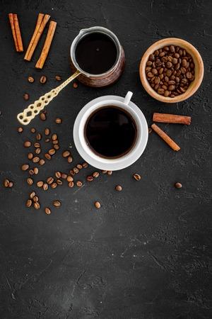 トルココーヒーポットでコーヒーを淹れます。黒の背景トップビュー。