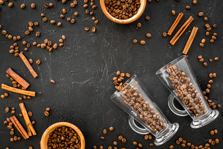 Ingredients for coffee. Roasted coffee beans and cinnamon on black background top view. Reklamní fotografie