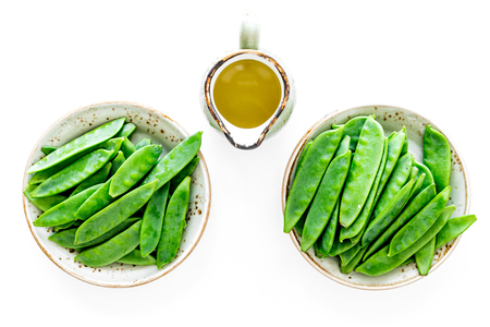 Fresh green pea pods on white background top view.