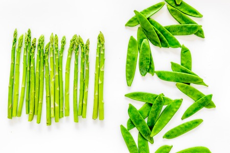 Fresh green pea pods and sprout of asparagus on white background top view
