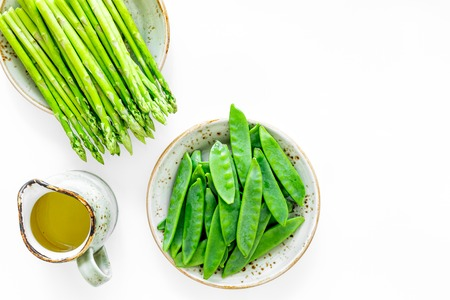 Fresh green pea pods, sprout of asparagus and mustard sauce on white background top view copyspace