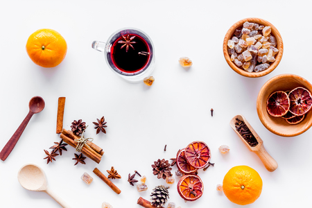 Hot mulled wine or grog cooking for new year celebration with oranges and spices ingredients on white background flat lay