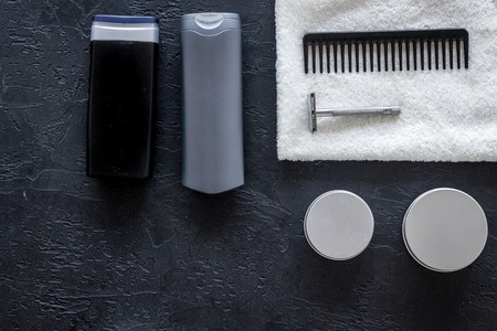 Mens cosmetics for hair care and shaving. Shampoo, gel, razor, wax on black background top view copyspace Stock Photo