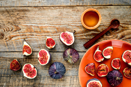 Plate of fresh blue figs on wooden background top view.