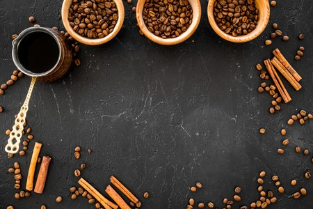 Brew coffee in turkish coffee pot. Black background top view. Stock Photo