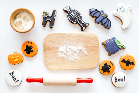Preparing halloween gingerbread cookies. Rolling pin, desk, flour on white background top view.