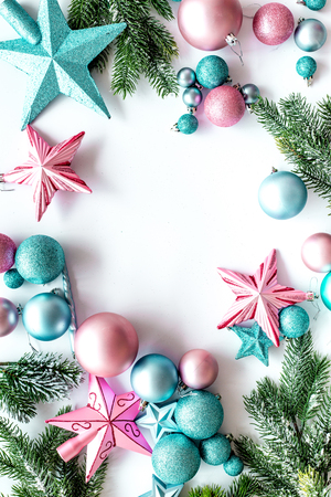 Christmas decoration frame. Pink and blue stars and balls near pine branches on white background top view.