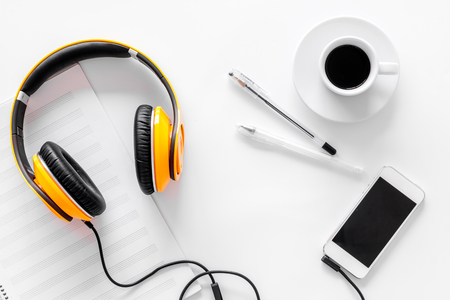 Compose music. Headphones, music notes, phone and coffee on white background top view.