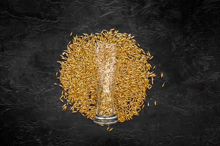 ビール黒ビール ガラス近く大麦の粒は背景平面図です。 写真素材