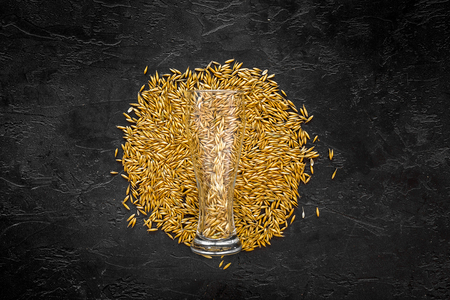 Grains of malting barley near beer glass on black background top view. Stock fotó