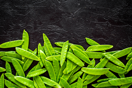Green pea pods pattern on black background top view.