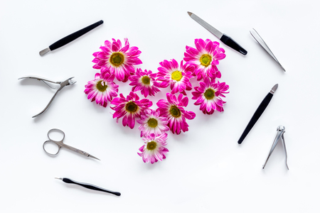 Hand care. Set of manicure tools and flowers on white background top view.