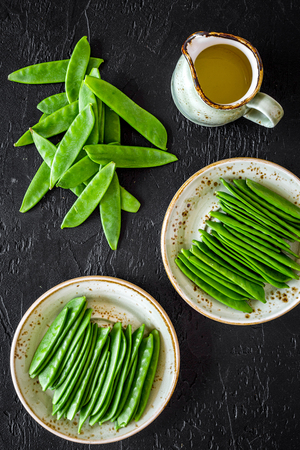 Green pea pods and asparagus near jug of oil on black background top view. Stock Photo