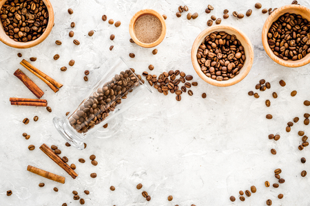 Ingredients for coffee. Roasted coffee beans and cinnamon on black background top view. Stock Photo