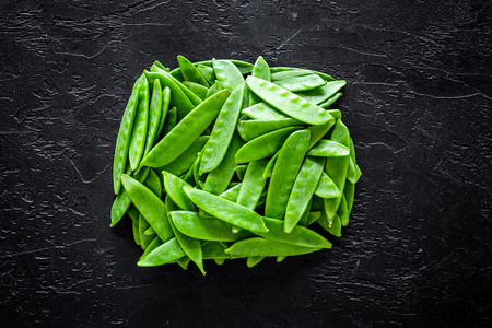Green pea pods on black background top view. Stock Photo