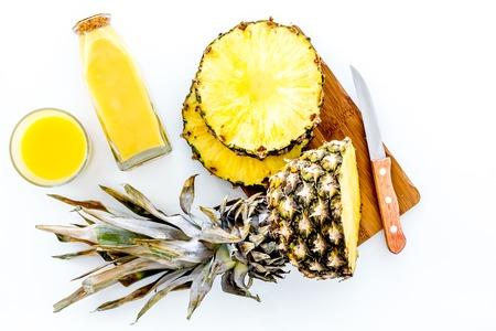 Ananassap bereiden. Snijd plakjes ananas met een mes op witte achtergrond bovenaanzicht. Stockfoto