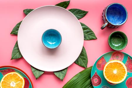 utensilios de cocina: Modelo coloreado de las tazas y de las placas adornado por las hojas y las frutas exóticas en la opinión superior del fondo rosado. Foto de archivo