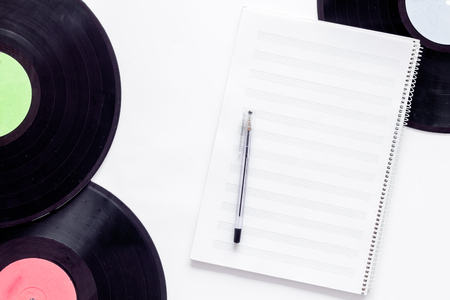 Compositors workplace. Vinyl records and music notes on white background top view.