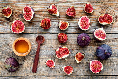 Fresh blue figs and honey on wooden background top view. 版權商用圖片