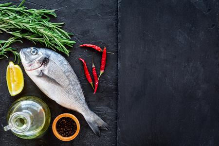 Preparazione di pesce fresco di mare. Vista dall'alto di sfondo nero. Archivio Fotografico - 87273224