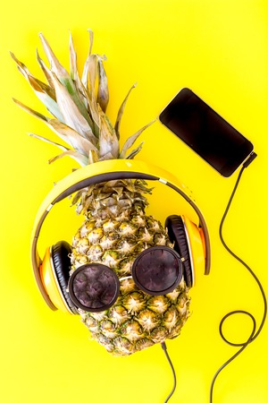 Stylish pineapple in sunglasses listen to music on the smartphone on yellow background top view.