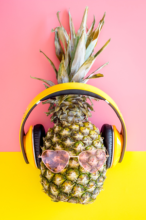Pineapple-hipster in pink glasses and headphones on yellow-pink background top view.