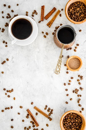 Cup of black coffee near coffee beans and cinnamon on grey background top view. Stock Photo