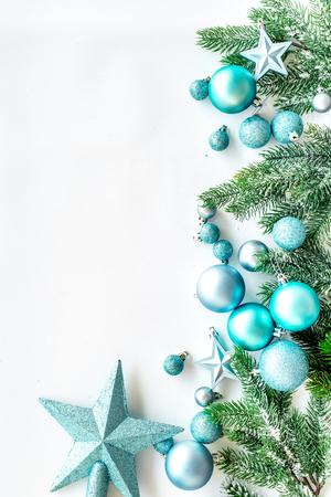 クリスマスのおもちゃのパターン。青い星と白い背景の上の松の枝に近いボール平面図です。
