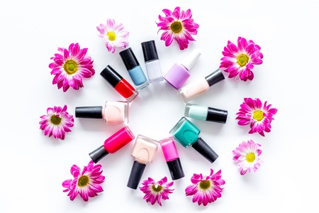Choose nail polish for manicure. Bottles of colored polish on white background top view