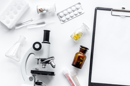 Microscope, pills and tablet on white background top view.