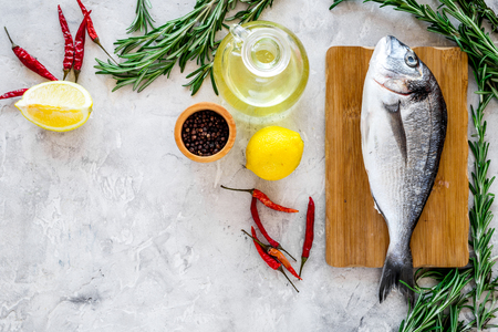 Preparing dorado with spices rosemary, pepper, chili, lemon. Grey background top view copyspace Stock Photo
