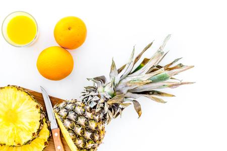 Vers ananassap in glas dichtbij ananas op witte hoogste mening als achtergrond Stockfoto