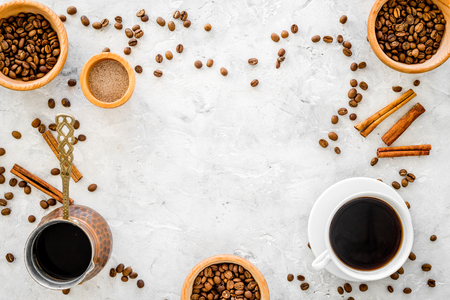 Cup of black coffee near coffee beans and cinnamon on grey background top view copyspace