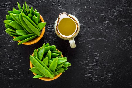 Green pea pods in bowls near jug of oil on black background top view copyspace