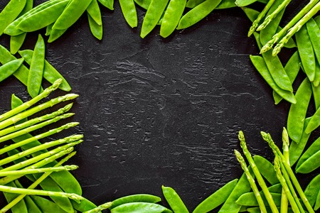 Green pea pods and asparagus on black background top view copyspace