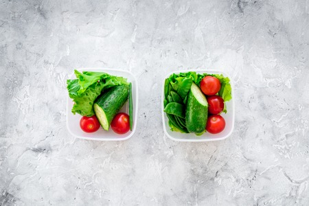 cucumbers: Healthy meal in containers. Summer salad with tomato and cucumber on grey background top view. Stock Photo