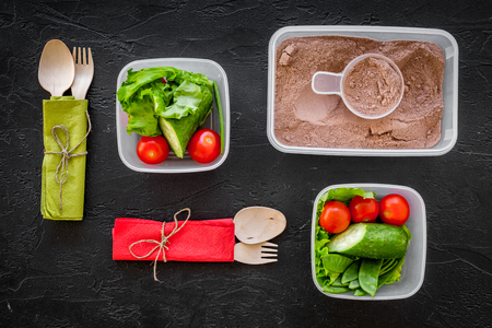 cucumbers: Healthy meal in containers. Summer salad with tomato and cucumber and protein for sportsman on black background top view