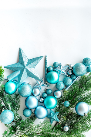 Christmas toys pattern. Blue stars and balls near pine branches on white background top view copyspace