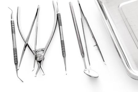 白い背景のキュヴェットの近くの歯科医の用具のセット 写真素材