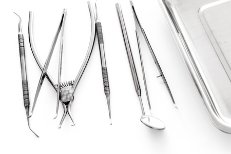 Set of dentists tools near cuvette on white background