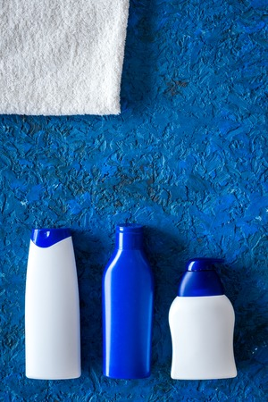 Shampoo and shower gel for men on blue background top view copyspace