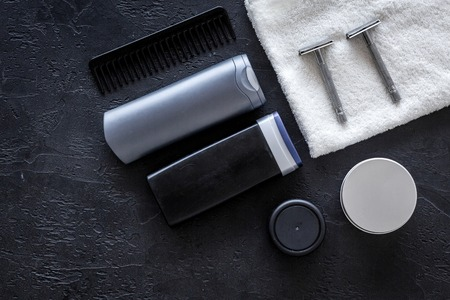 Mens cosmetics for hair care and shaving. Shampoo, gel, razor, wax on black background top view Stock Photo