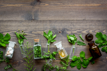 Homeopathy. Leaves of healing herbs, bottles and pills on wooden background top view.