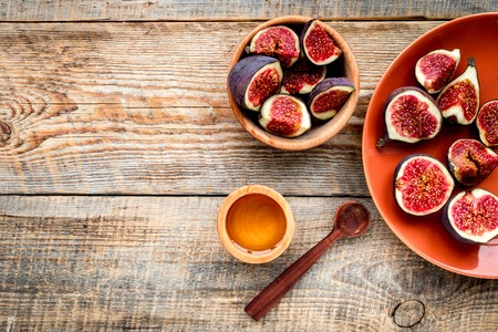Fresh blue figs in bowl and honey on wooden background top view. 版權商用圖片