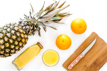 Vers ananassap in glas en fles op witte hoogste mening als achtergrond.