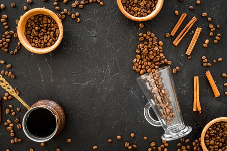 Ingredients for coffee. Roasted coffee beans and cinnamon on black background top view. Imagens